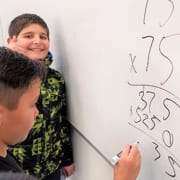 Boys & Girls Clubs members do math on whiteboard