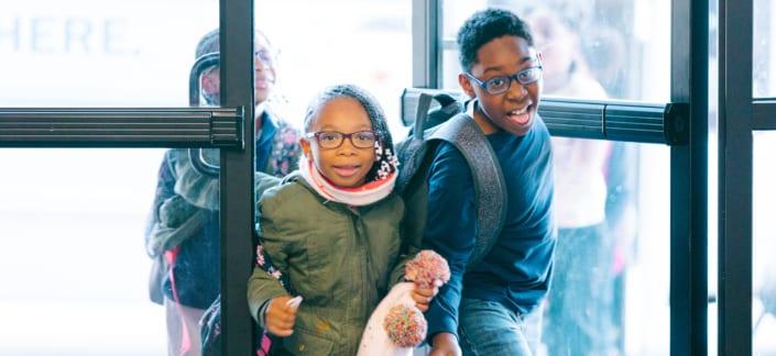 Two children in winter coats coming through doors of Club