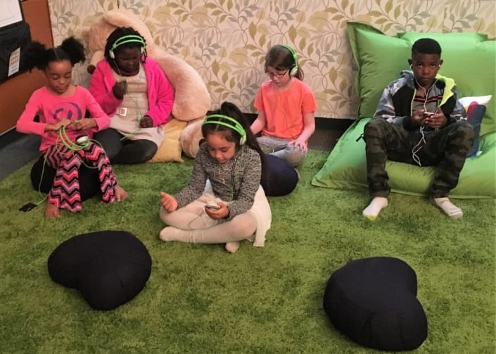 Five children sit, listen to music, and meditate in the Regence Club Peace Room