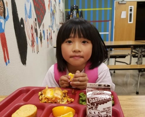 Youth member eats meal in Kids Cafe at Inukai Family Club