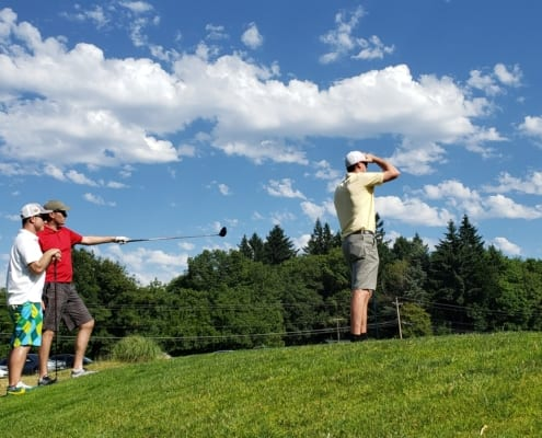 Three golfers gaze out at course against a blue sky with scenic clouds, one points with club