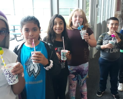 Group of 6 youth sips on tropical summer slushies with paper straws.