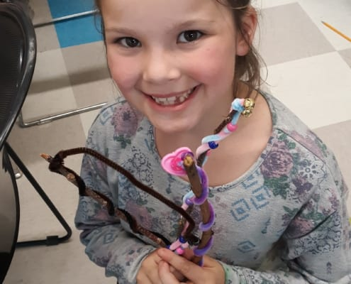Girl smiles at camera holding her pipe cleaner craft project