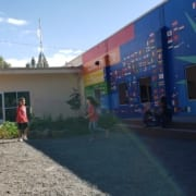 Kids run through inukai play space with entry doors and the rainbow-hued mural in the background.