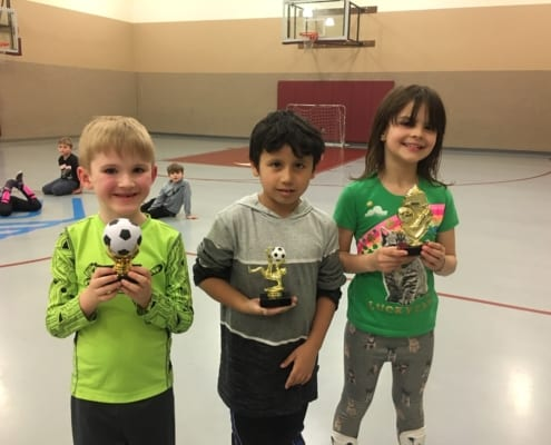 Three 1st-6th grade Club members holding Indoor Soccer Trophies