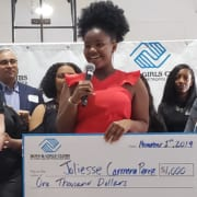 Joliesse Carmona Perez on stage giving speech with scholarship check immediately after she was announced as the Portland Metro Youth of the Year by judges on stage behind her..