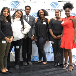 Youth of the Year Candidates stand in a group against the Boys & Girls Clubs branded backdrop on the stage.