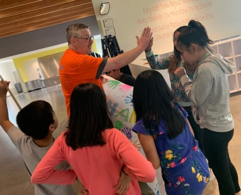 "Youth at Rockwood give long-time volunteer Mr. Scott a ""thank you"" banner as he gives one of them a high five."